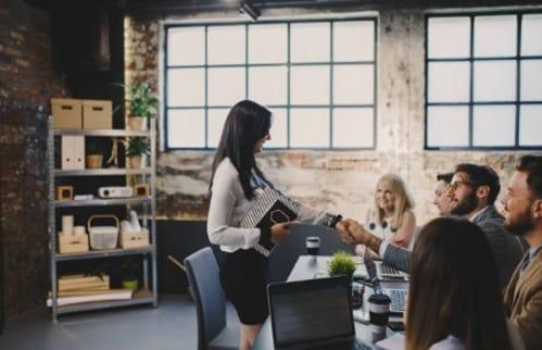mujer capacitando a nuevo personal en sala de juntas