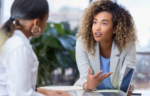 mujeres hablando en una mesa de frente