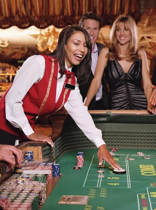 mujer diles en mesa de juego con pareja atras