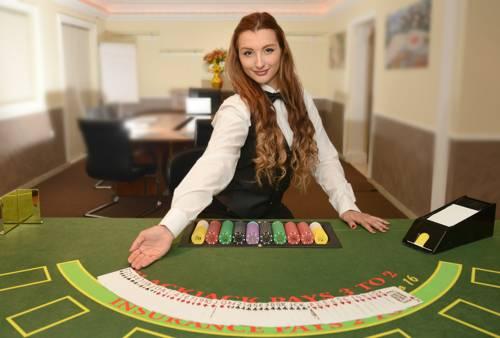 Mujer dealer en mesa de juego de casino