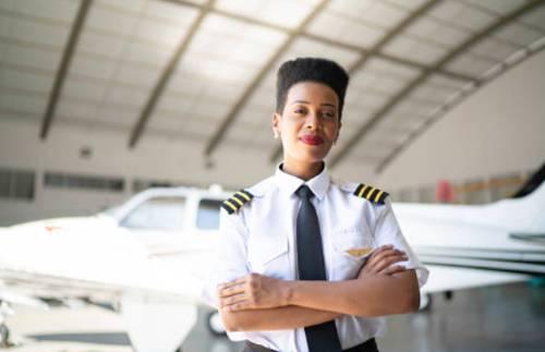Mujer piloto aviador delante de un avion