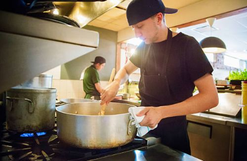 estudiantes cocineros aprendiendo a cocinar en escuela de gastronomia